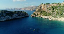Aerial View Above The Mediterranean Sea, With Kayak And People In The Water Next To The Edge Of A Cliff 4K