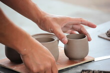 Cropped Hands Of Person Holding Earthenware On Table