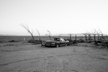 Grayscale Photo Of Car Parked In Desert
