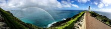 Panoramic View Of Rainbow Over Sea Against Cloudy Sky
