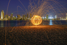 Orange Steel Wool Near Body Of Water And City During Nighttime