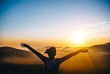 Silhouette Of Person Raising Their Hands During Sunset On Mountain Peek