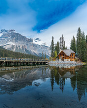 Brown Wooden House On Bridge Near Snow Covered Mountain With Reflection On Water