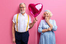 Man Give Heart Shaped Balloon As Present To Mature Happy Woman, Make Surprise To Wife. Woman Closing Mouth In Shock. Isolated Pink Background