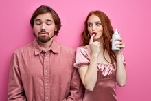 Woman Holding Whipped Cream In Hands, Smeared Cream On Guy's Nose, Playing Flirting With Him Isolated On Pink Background