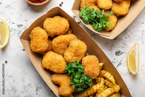 Fototapeta Tasty nuggets and french fries in paper box on light background obraz