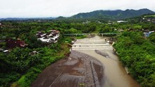 Aerial View Of A Massive Raft On The River In Bali. Drone Footage Of River Water Going Over Cascading Weir. River Water Move Down From With A Water Filled Dam After Heavy Floods And Rains