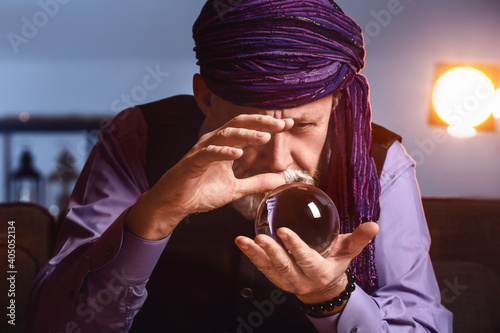 Fototapeta Male fortune teller with crystal ball at home