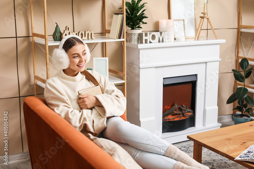 Fotografie, Obraz Young woman with book near fireplace at home