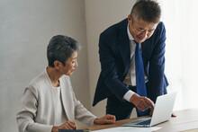 仕事をするシニア世代のビジネスマンとビジネスウーマン