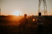 Men Near Transmission Tower During Sunset
