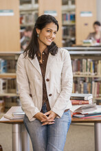 Mixed Race Woman Leaning On Library Table