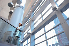 Caucasian Businesswoman Leaning On Railing In Lobby