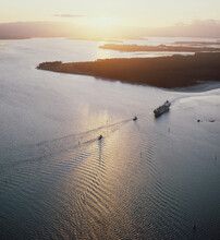 Aerial Of Cargo Ship Entering Harbour Mouth At Sunset