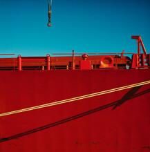 Crane Hook Against Blue Sky Decending To Red Ship Tied To Dock At Port