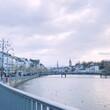 Leinwandbild Motiv Bridge Over River Against Buildings In City