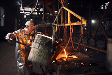 Production Of Steel Castings In An Industrial Smelter Company. Foundry Worker Filling Molds With Liquid Steel.