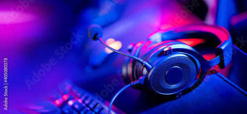 Obraz Professional headphones with microphone for video games and cyber sports on background of gaming monitor - fototapety do salonu