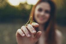 Romantic Woman With Praying Mantis On Her Hand Outdoors In The Meadow