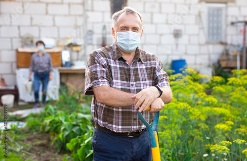 Fototapeta Man professional horticulturist in protective mask with garden shovel working at
