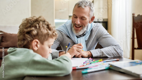Obraz Happy grandfather enjoying spending time with his little grandson, drawing with colored felt tip pens on paper while sitting at table - fototapety do salonu