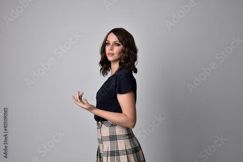 Close up portrait of pretty brunette woman wearing tartan skirt and blouse Fototapete