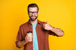 Photo portrait of bearded millennial in eyewear showing like sign keeping beverage cup takeaway isolated on bright yellow color background