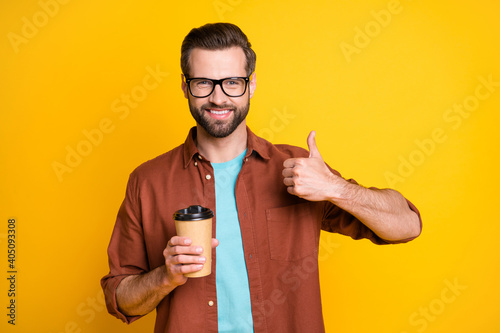 Fototapeta Photo portrait of bearded millennial in eyewear showing like sign keeping beverage cup takeaway isolated on bright yellow color background obraz