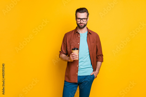 Obraz Photo portrait of bearded man in glasses keeping cup with coffee in casual clothes isolated on vivid yellow color background - fototapety do salonu