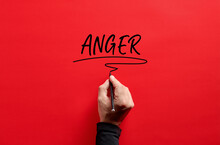 Male Hand Writing The Word Anger On Red Background. Anger Management