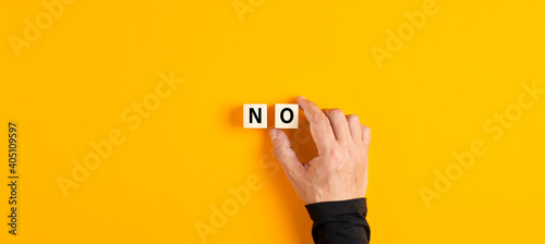 Canvas Print The word no written on wooden cubes with male hand placing the cubes