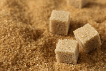 Brown Cane Sugar Crystals And Cubes Of Refined Cane Sugar Closeup.