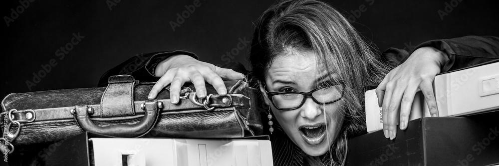 Fototapeta Segretaria  bionda con occhiali da vista, vestita con  di nero e disperata e preoccupata in mezzo a tutti i documento disordinati del suo ufficio  , isolata su sfondo nero
