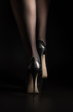 Legs Of A Woman In High Heels In Black Tights On A Black Background. Side View With Space To Copy.