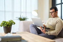 Close To Home. Handsome Latin Middle Aged Businessman In Eyeglasses Using Laptop While Working From Home