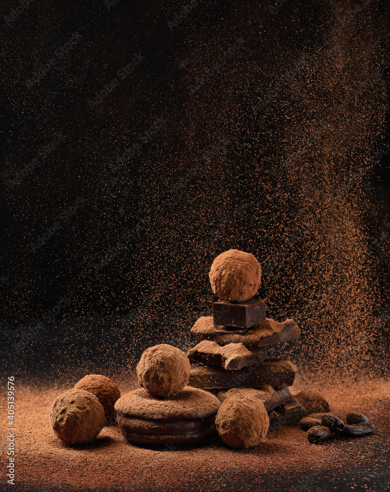 Fototapeta Pieces of chocolate with sweets truffle with air flying cocoa powder on a dark background.