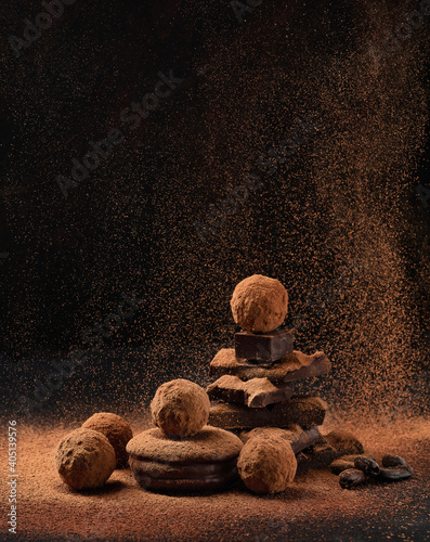 Pieces of chocolate with sweets truffle with air flying cocoa powder on a dark background.