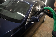 Car Drying Process After Washing. Man With Vacuum Cleaner Removes Water Droplets From Car. Professional Auto Wash Concept