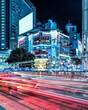 Leinwandbild Motiv Light Trails On City Street By Buildings At Night
