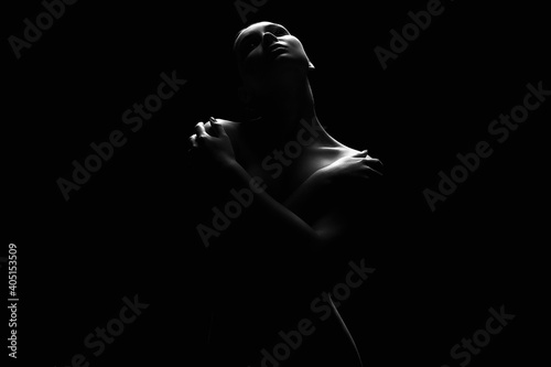 Nude Woman silhouette under light in the dark