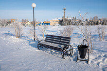 Snow Covered Wooden Bench In The Park In Winter
