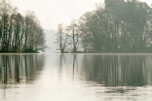 Obraz jezioro w Straszynie w marcu, odbicie w tafli jeziora - fototapety do salonu
