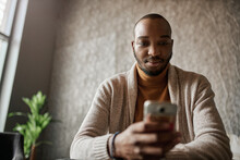 Black African Business Man Looking Down Reading Texts On Mobile Phone