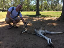 Portrait Of Man Crouching With Kangaroo Resting At Park