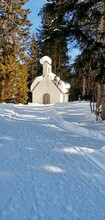 Snow Covered Trees By Chapel Against Clear Sky