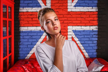 Fashion Glamorous Portrait Of A Girl Model With White Sweater On Wall Background With A British Flag