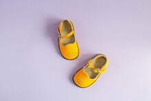 Bright Yellow Baby Shoes On Lilac Background With Copyspace. Baby Clothes Concept. Top View, Flat Lay
