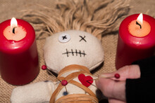 Cropped Hand Inserting Straight Pin In Voodoo Doll