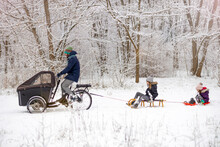 Man On A Cargo Bike Carries Kids On A Sleigh In Winter