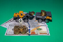 Miniature People Business Man Stand On Stack Coin And Us Dollar Bill With Yellow Loader Is Scooping Coins To Put A Dump Truck Is In The Back, On Green Background.